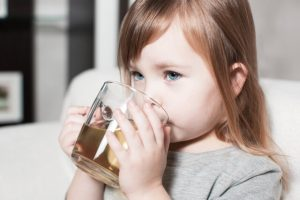 A child is drinking medicine for a toothache.