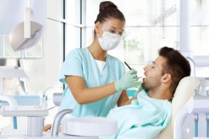 The dentist performs gum surgery on the patient.